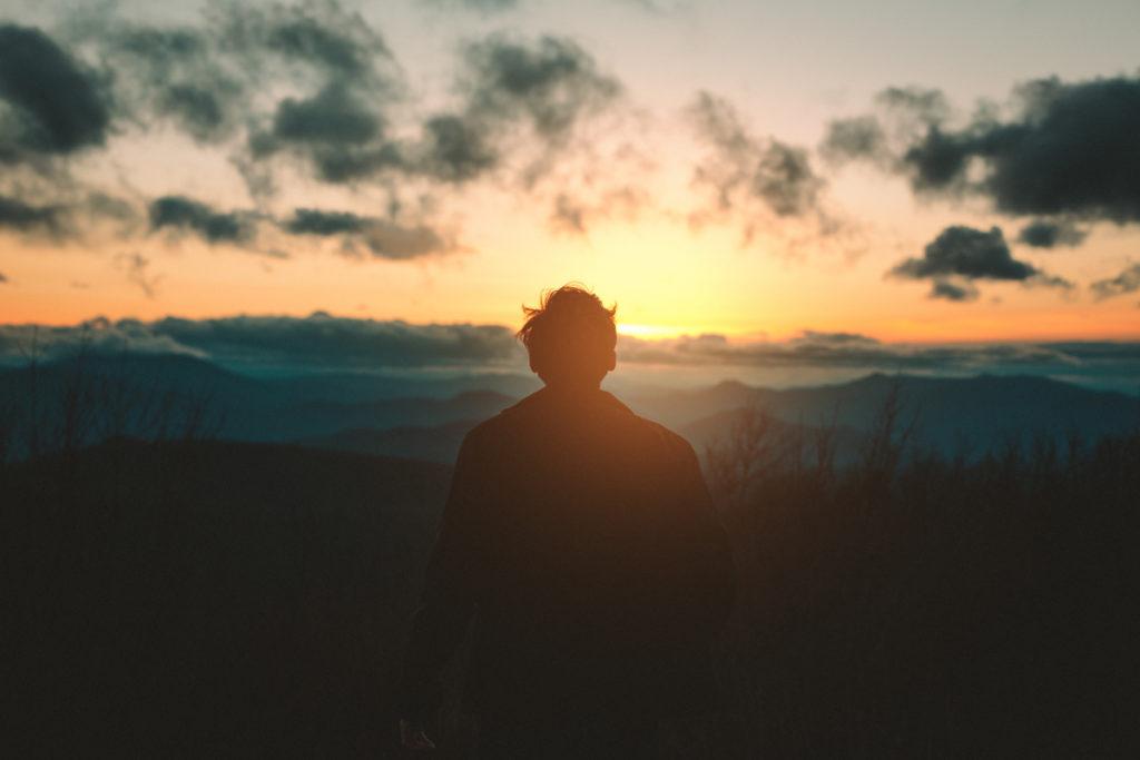 Một người đàn ông nhìn chằm chằm vào bình minh ở đường chân trời