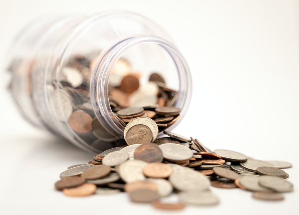 Jar full of coins dropping out.