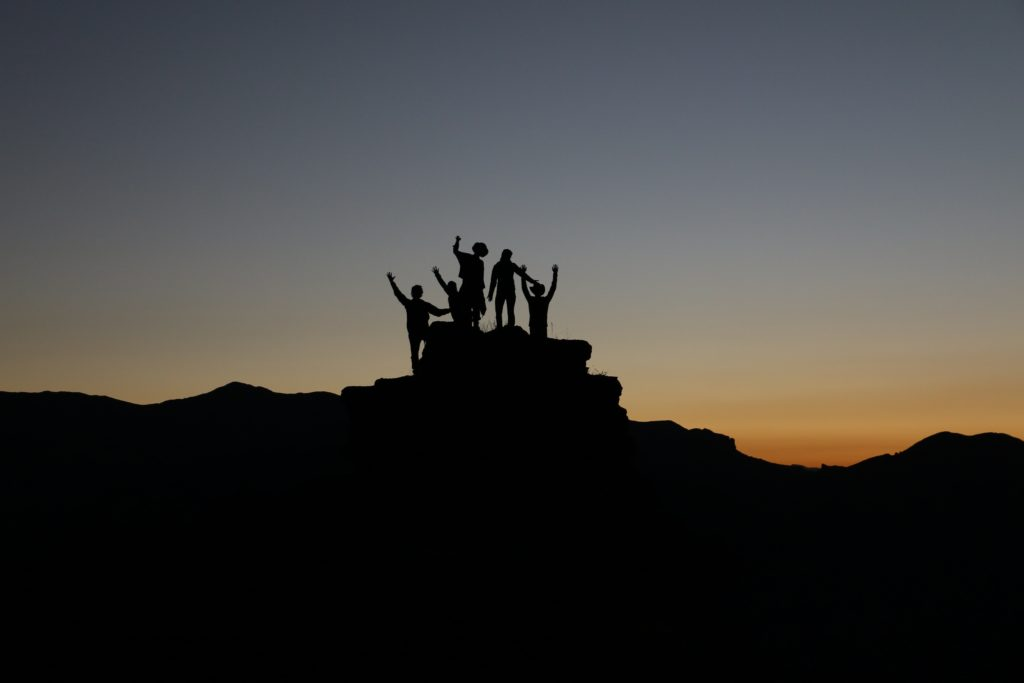 Group of individuals on the top of a hill raising their hands in the sunset.