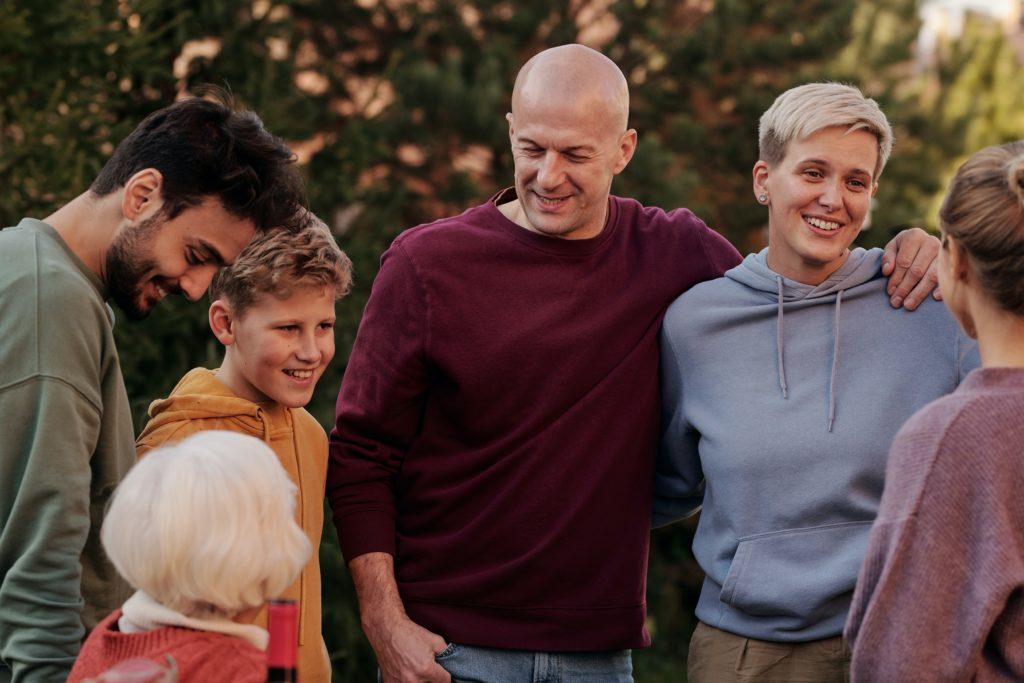 Một gia đình gồm các thành viên khác nhau ở mọi lứa tuổi đang mỉm cười với nhau.